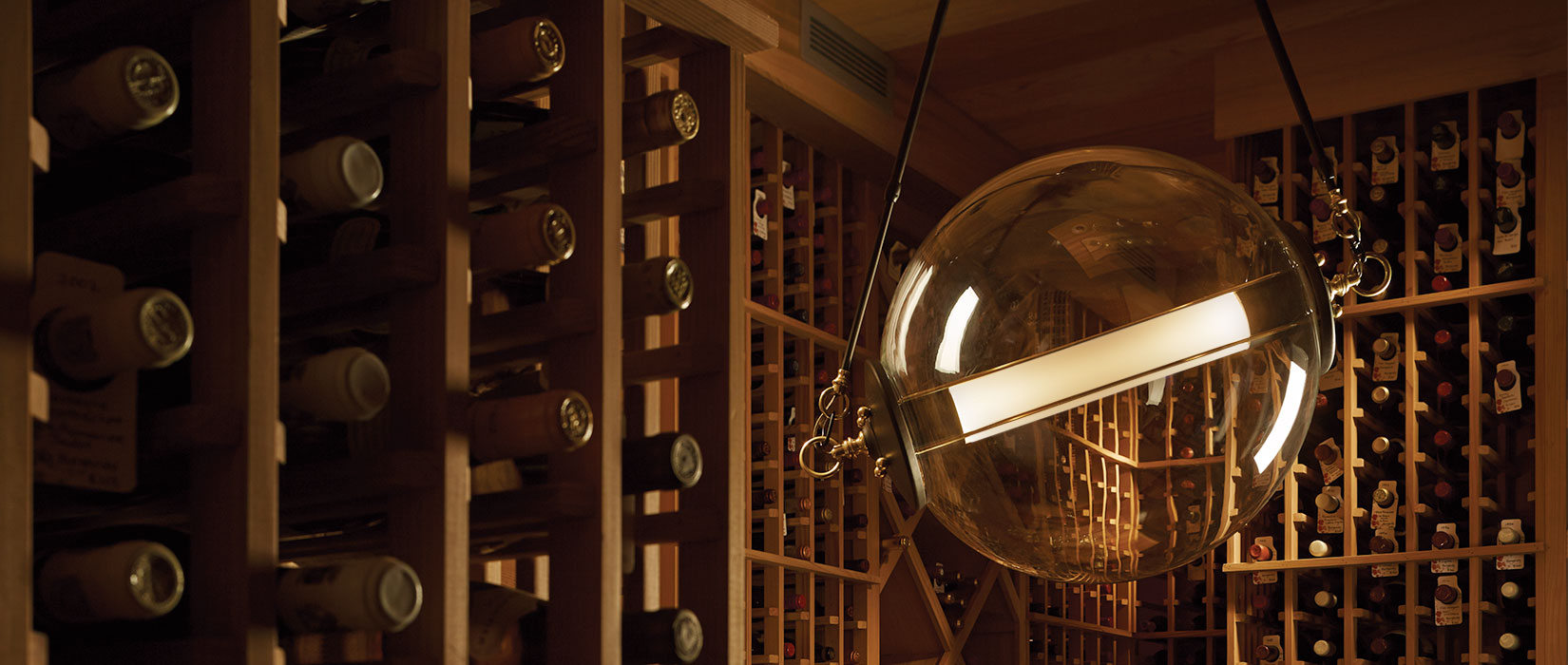Otto Sphere Pendant hung in an industrial wine cellar setting
