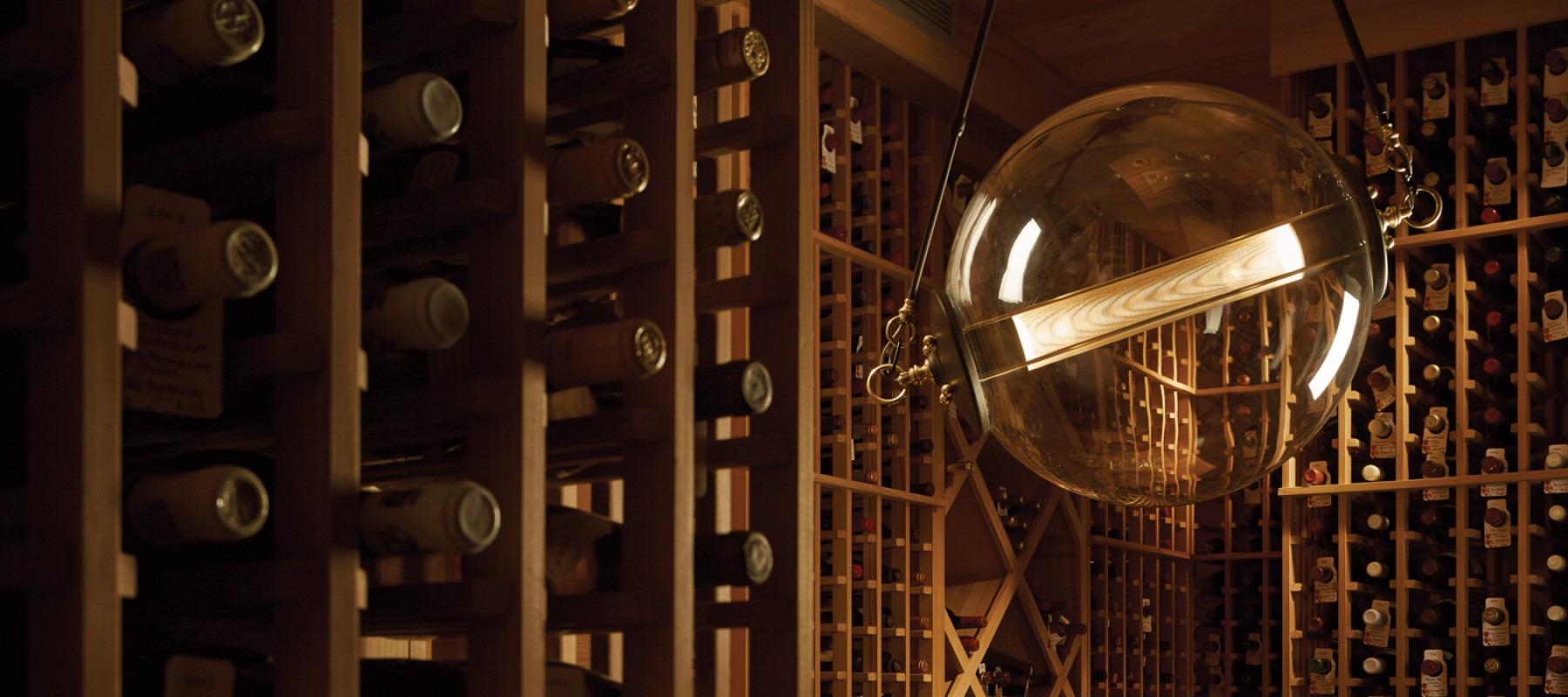 Introducing the Otto Sphere Pendant hung in an industrial setting in a wine cellar